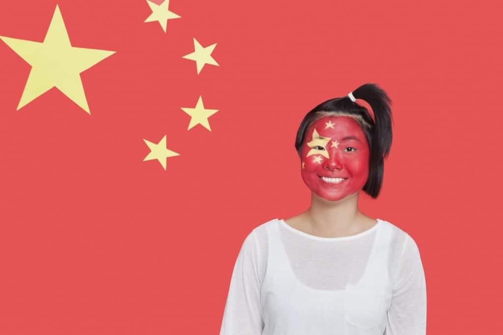Kvinde med det kinesiske flag malet i ansigtet. I baggrunden ses det kinesiske flag.